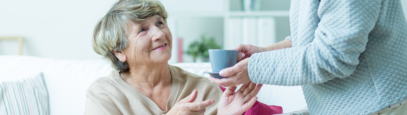 senior taking cup of tea from caregiver