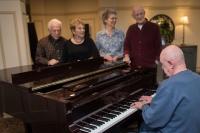 residents gathered around piano