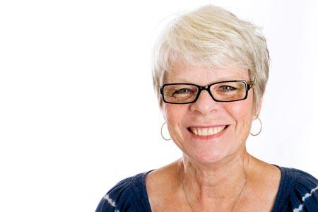 Senior woman smiling at camera, wearing glasses