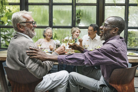 Group of seniors caround a dinner table, two men in the foreground are clinking glasses