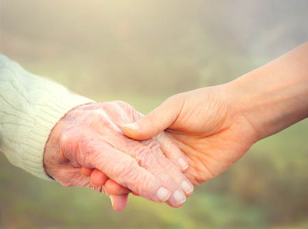 Two hands grasped, one older and one younger