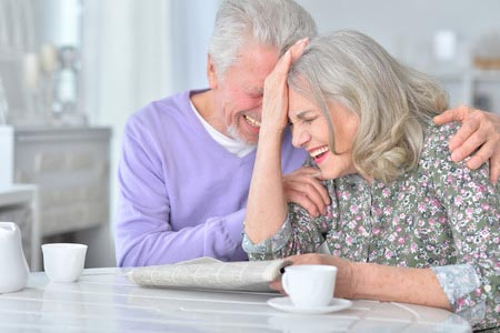Senior couple laughing together at a table