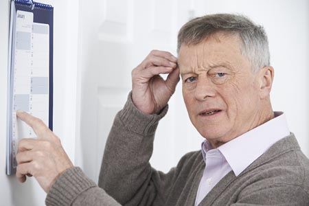 Man pointing at a calendar looking confused