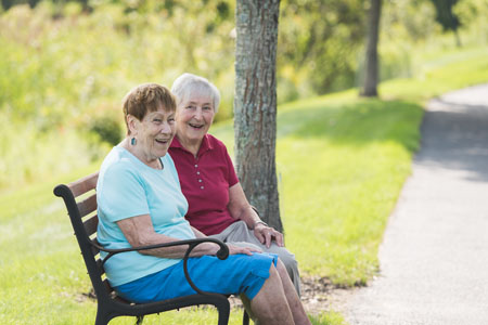 Katie and Reba smiling on a bench