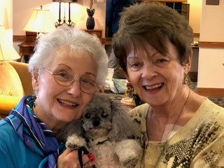 Two residents holding a dog between them