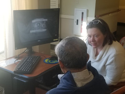 Senior man and woman at a computer listening to music
