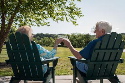 Senior Couple enjoying wine on the patio in Adirondack Chairs