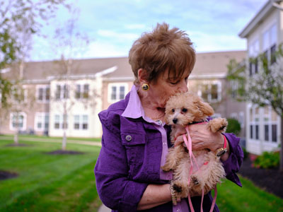 Joyce kissing her puppy ginger spice on the head, holding the puppy in front of the senior living community