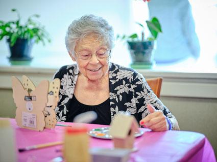 Senior Woman making a birdhouse