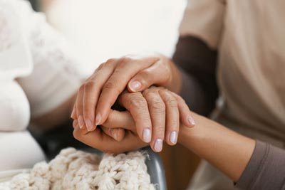 social worker holding hands of senior woman