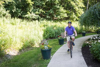 Senior man riding bike with helmet