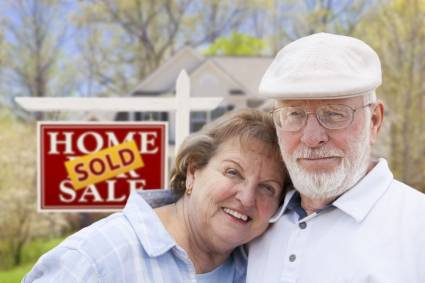 senior couple in front of sold house